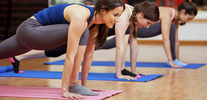 Beautiful young Hispanic women working out and enjoying their yoga class in a gym